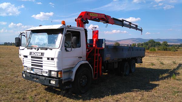 бял сканиа камион с ремарке и кран за повдигане