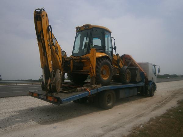 камион с широка платформа за превозване на трактор